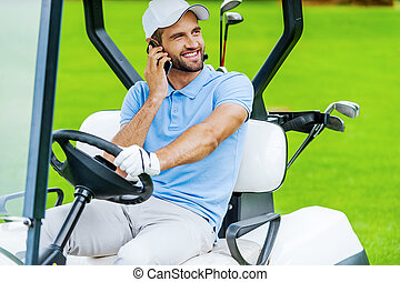 Great day to play golf! Handsome young smiling man driving a...