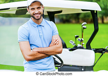 Golf is my favorite game! Handsome young man keeping arms...