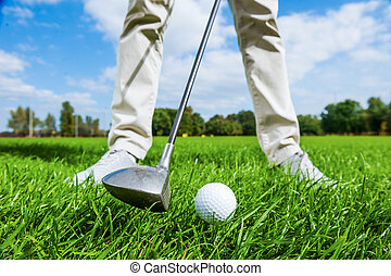 Teeing off. Close-up of male golfer teeing off while standing on golf course