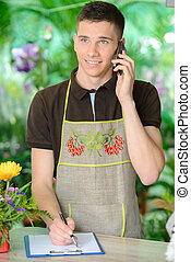 Florists - Florist man working with flowers at a greenhouse...