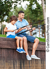 Fishing together Cheerful father and son fishing while...