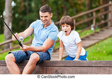 It is a big fish Happy father and son fishing together while...