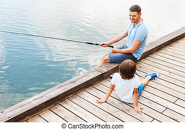 My father is the best in fishing. Top view of cheerful father and son fishing together while sitting at the riverbank