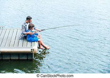 Father and son fishing. Top view of father and son fishing...