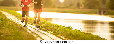Couple running outdoors, at sunset, by a river, staying...
