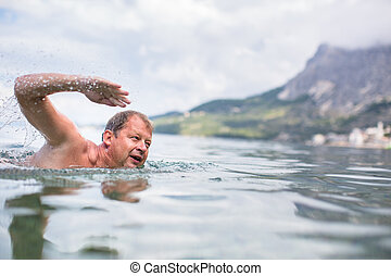 Senior man swimming in the SeaOcean - enjoying active...