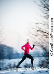 Winter running - Young woman running outdoors on a cold...