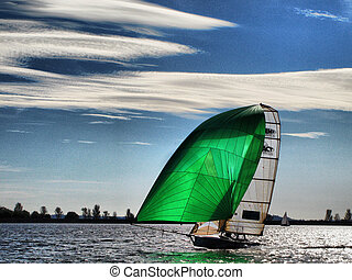 Dinghy sailboat sailing on a lake under a blue sky