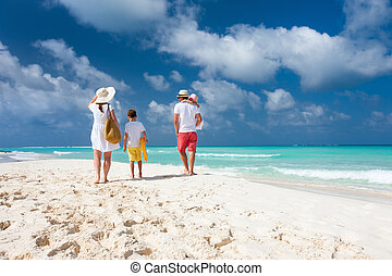 Family beach vacation - Back view of a happy family on...