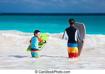 Father and son surfing - Father and son running towards...