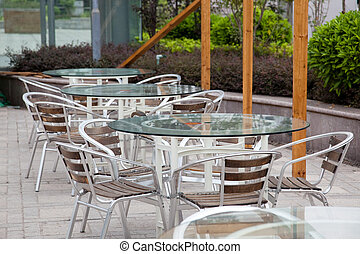 Outdoor cafe - Tables and chairs ready for diners at an...