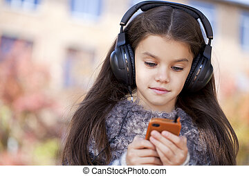 Beautiful little girl listening to music on headphones in...