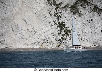 sailboat motoring along on the sea under white cliffs close...