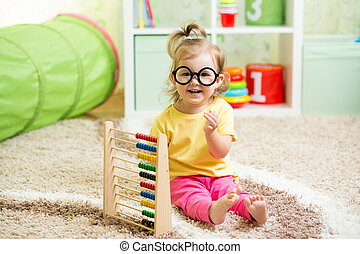 kid weared eyeglasses playing with abacus