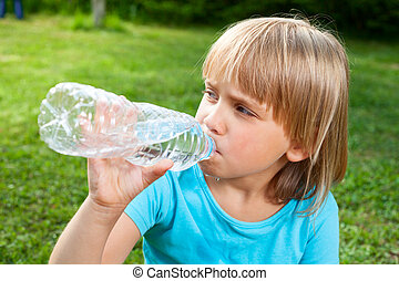 Child drinking water outdoor - Cute little girl drinking...