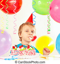Little boy in festive hat with birthday cake with whistle and holiday balloons