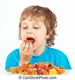 Little child eating jelly candies on white background