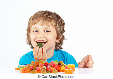 Little boy eating candies on white background