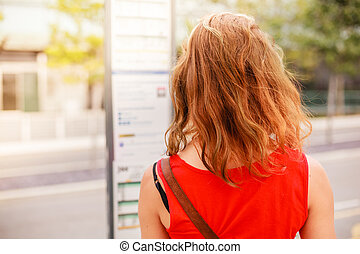 Woman looking at bus timetable - A young woman is studying a...