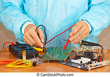 Master checks electronic hardware with a multimeter in...