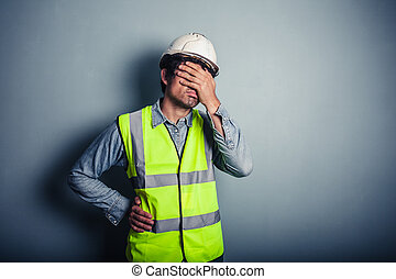Engineer covering his face - A young engineer wearing a high...
