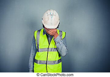 Engineer in high vis covering face - A young engineer...
