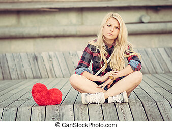 Sad lonely girl sitting on wood planks near to a big red...