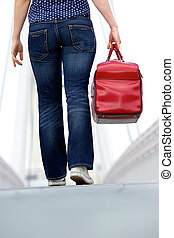 Woman walking with bag outdoors - Low angle rear view woman...