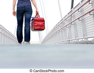 Woman walking with bag outdoors - Low angle woman walking...