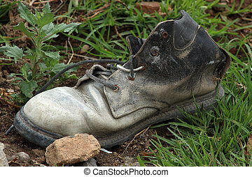 Worn Out Shoe - A worn out shoe next to a stone in...