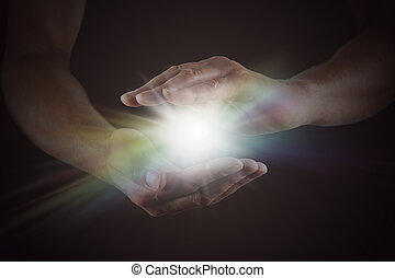 The Spark of Life - Male hands emerging from darkness,...