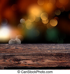 Old weathered wooden board with a sparkling bokeh of party...