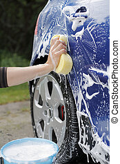 Car wash - A Hand washing a blue car with a sponge