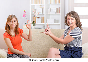 Deaf woman learning sign language - Smiling deaf woman...