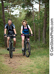 Happy couple cycling in nature