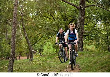 Healthy couple enjoying a bike ride in nature - Portrait of...