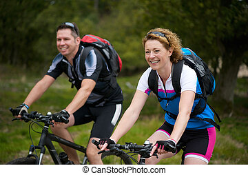 Man and woman enjoying a bike ride in nature - Portrait of a...