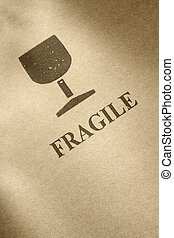 "Fragile - ""Fragile\"" symbol printed on brown cardboard"