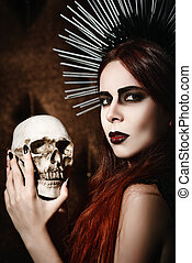 Portrait of beautiful gothic girl holding the skull -...