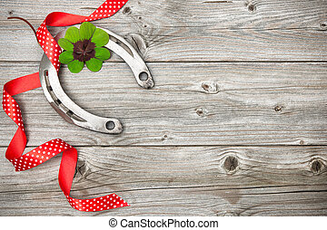 Horseshoe, shamrock and red ribbon on old wooden - Holidays...