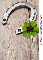 Horseshoe with a shamrock on old wooden background