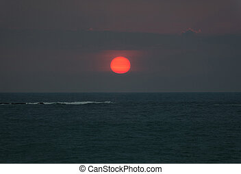 Bright sunset with large red sun under the ocean surface and...
