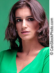 Beautiful woman with brown curly long hair in green dress