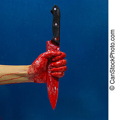 A bloody hand holding a large blood covered knife