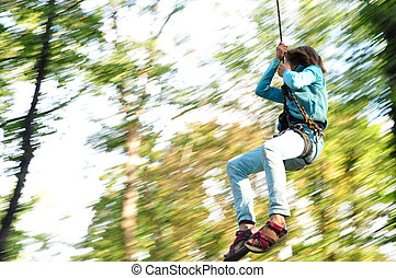 child in a climbing adventure activity park - teenager...