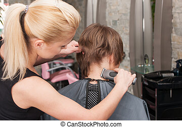 Female hairdresser cutting hair of man client using trimmer. back view of man sitting in chair in hair salon