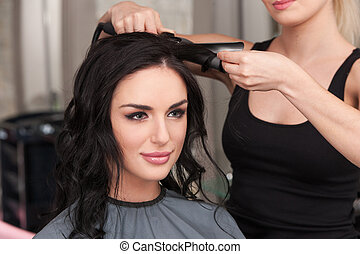 young woman getting her hair curled by stylist at parlor....