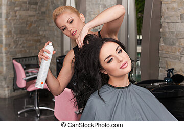 Young female hairdresser applying spray on client's hair....