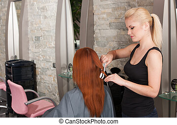 Hairdresser straightening red hair with hair irons. back view of redhead lady straightening hair at hairdresser salon