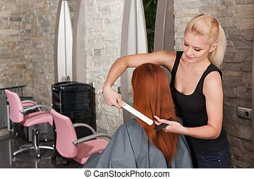 Blond hairdresser straightening red hair with hair irons. back view of redhead lady straightening hair at hairdresser salon